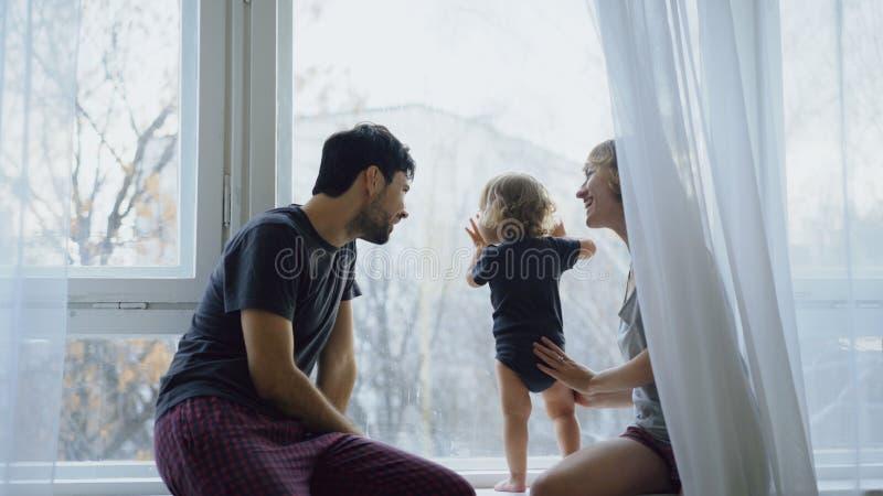 Lycklig familj med ungt gulligt dottersammanträde på fönsterbrädan som hemma spelar och ser i fönster royaltyfria foton