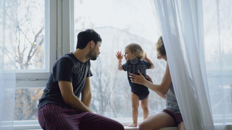 Lycklig familj med ungt gulligt dottersammanträde på fönsterbrädan som hemma spelar och ser i fönster arkivfoton