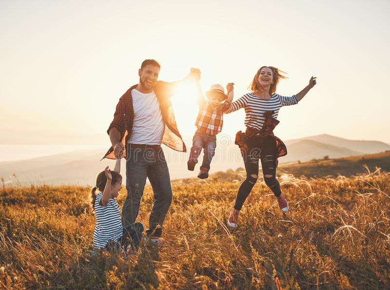 Lycklig familj: moder, fader, barn son och dotter på solnedgång royaltyfri foto