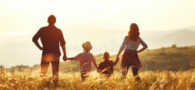 Lycklig familj: moder, fader, barn son och dotter p? solnedg?ng arkivbild