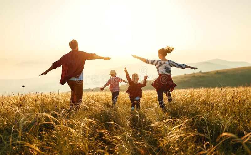 Lycklig familj: moder, fader, barn son och dotter p? solnedg?ng arkivbilder