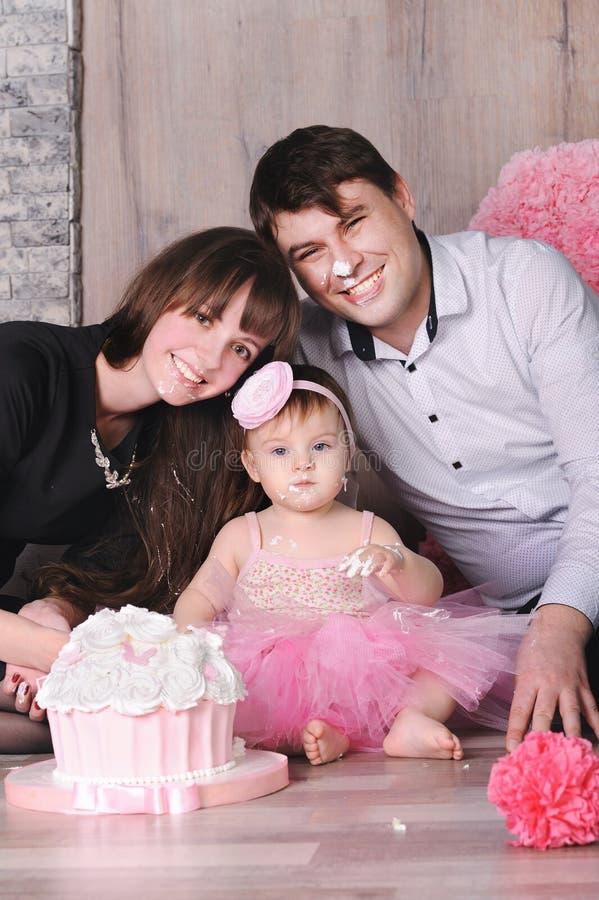 Lycklig familj - moder, fader och dotter som firar den första födelsedagen med kakan royaltyfria foton