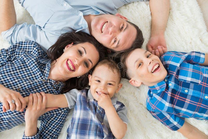 Lycklig familj, moder, fader och två söner som har gyckel som ligger på golvet, övresikt arkivbilder