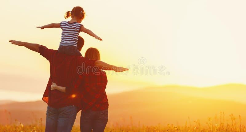 Lycklig familj: moderfader och barndotter på solnedgång arkivfoto