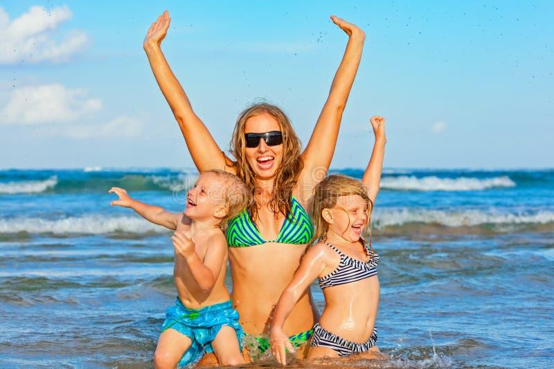Lycklig familj - modern med ungar på sommarstranden semestrar royaltyfri fotografi