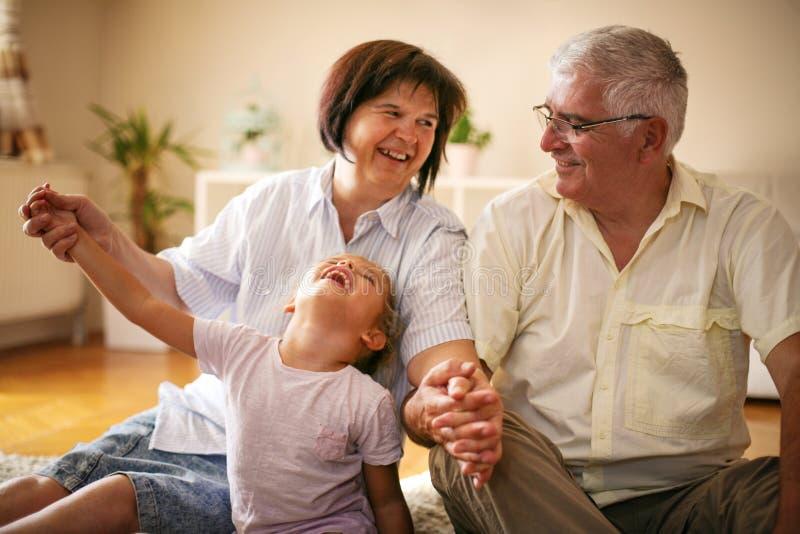 lycklig familj Morföräldrar med den hemmastadda sondottern royaltyfria foton