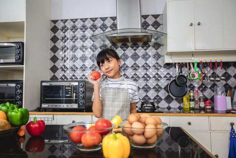Lycklig familj och deras liten dotter som tillsammans lagar mat i köket royaltyfri foto