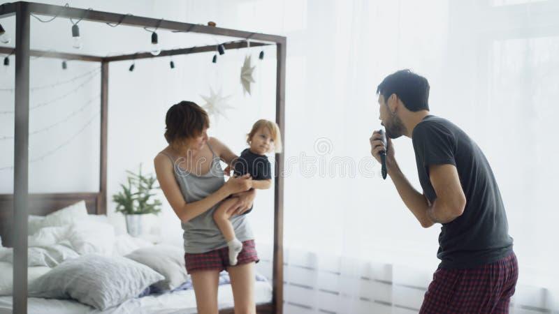 Lycklig familj och liten gullig dotter som dansar nära säng i sovrum medan famter som hemma sjunger royaltyfri foto