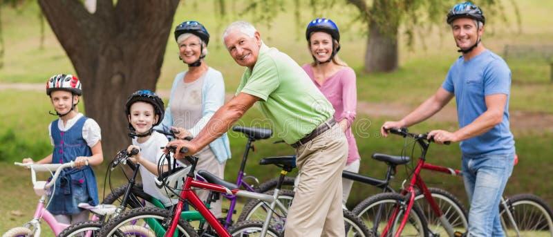 Lycklig familj på deras cykel på parkera fotografering för bildbyråer