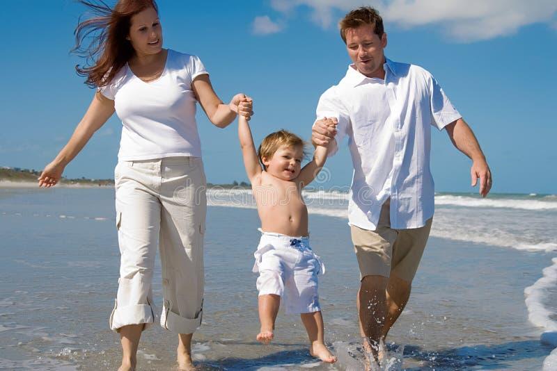 Lycklig familj på en strand arkivfoton