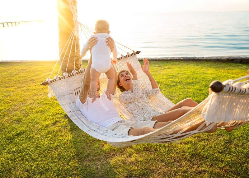 Lycklig familj på en tropisk ö på solnedgånglögnen i en hängmatta och att spela med deras son royaltyfri fotografi
