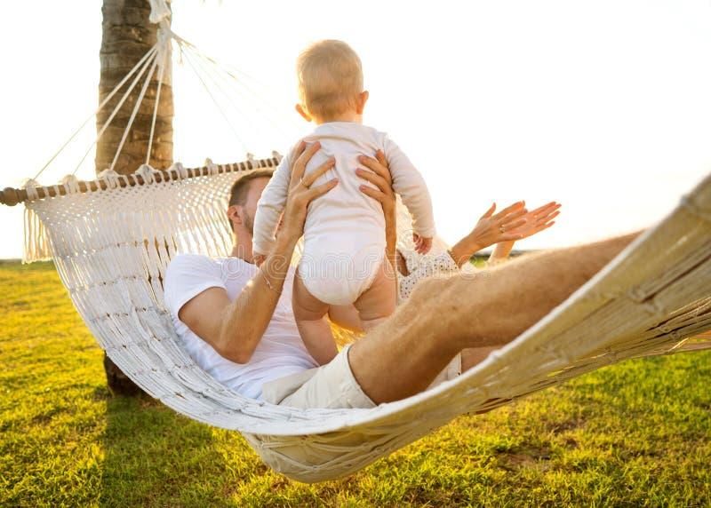Lycklig familj på en tropisk ö på solnedgånglögnen i en hängmatta och att spela med deras son royaltyfria foton