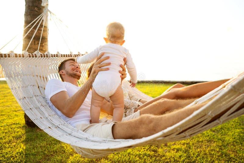Lycklig familj på en tropisk ö på solnedgånglögnen i en hängmatta och att spela med deras son royaltyfri foto