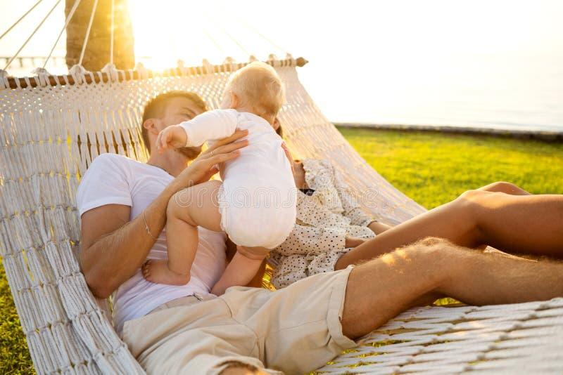 Lycklig familj på en tropisk ö på solnedgånglögnen i en hängmatta och att spela med deras son arkivbild