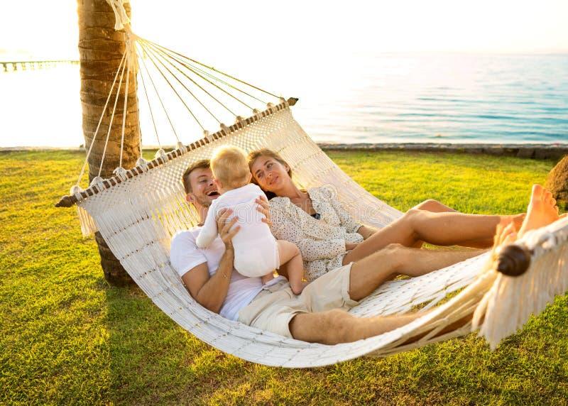 Lycklig familj på en tropisk ö på solnedgånglögnen i en hängmatta och att spela med deras son arkivbilder