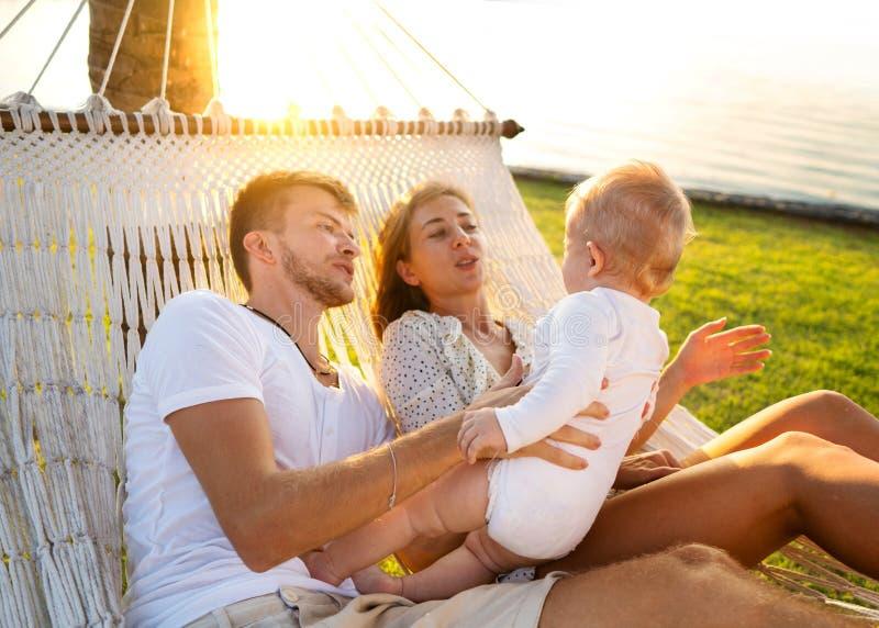 Lycklig familj på en tropisk ö på solnedgånglögnen i en hängmatta och att spela med deras son arkivfoton