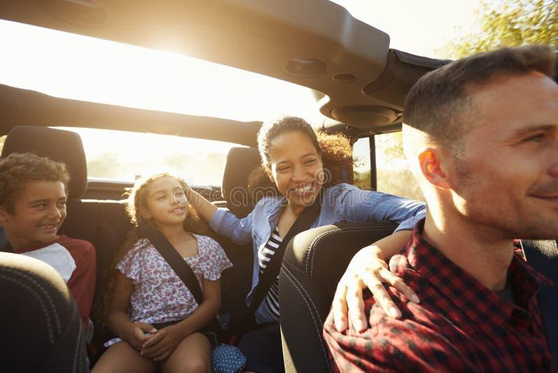 Lycklig familj på en vägtur i bil, främre passagerare POV arkivbild