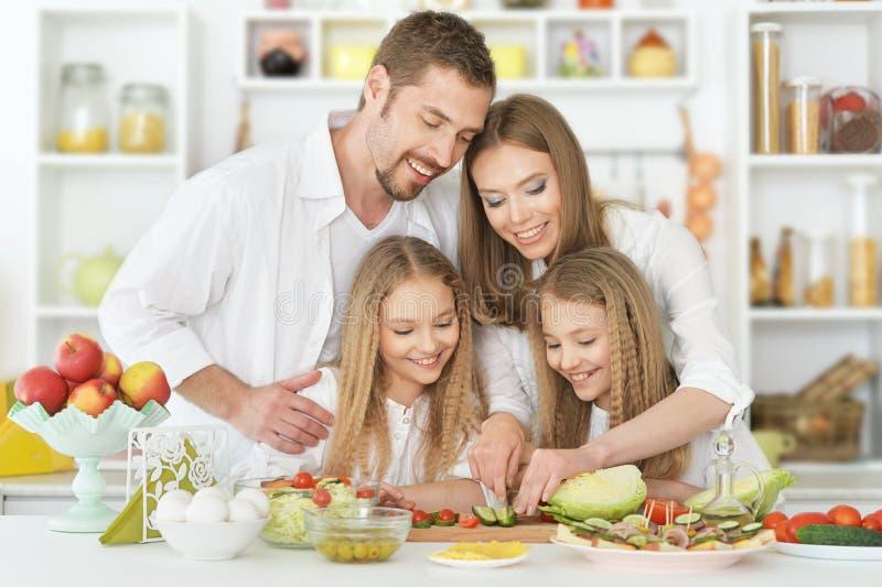 Lycklig familj på kök arkivbild