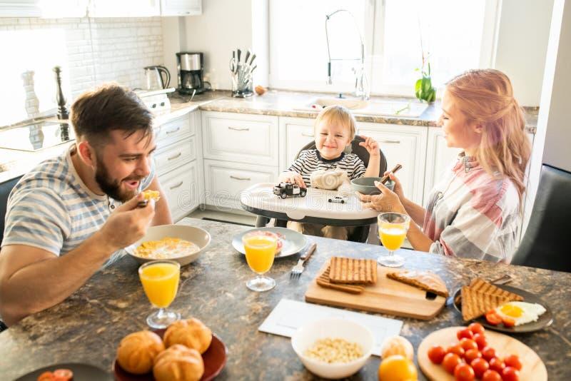Lycklig familj på köksbordet i morgon royaltyfri bild