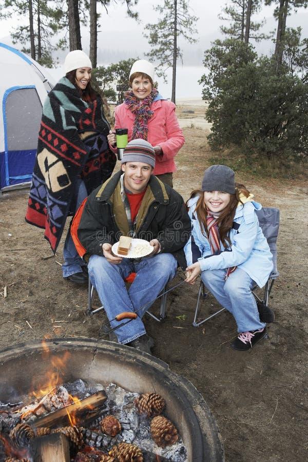 Lycklig familj på lägereld i vinter royaltyfri foto