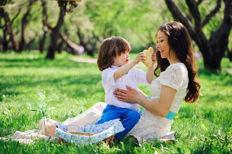 Lycklig familj på picknicken för moderdag Mamma- och litet barnson som äter sötsaker som är utomhus- i vår fotografering för bildbyråer