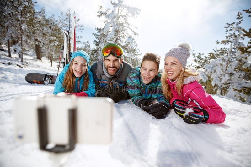 Lycklig familj på skidåkning som tar selfie på snö royaltyfri bild