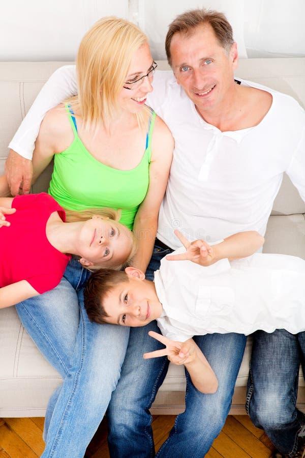 Lycklig familj på soffan royaltyfri fotografi