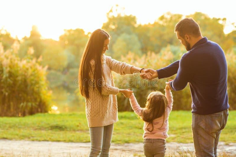 Lycklig familj på solnedgången i skoginnehavhänderna i en cirkel royaltyfri bild