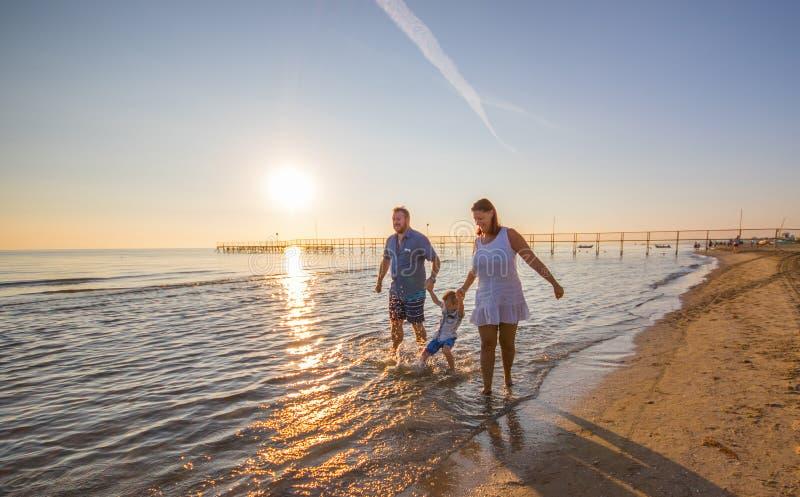 Lycklig familj på stranden på solnedgång arkivfoto