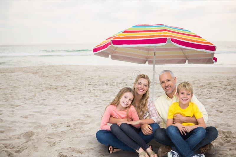 Lycklig familj på stranden under en kulör slags solskydd royaltyfri bild