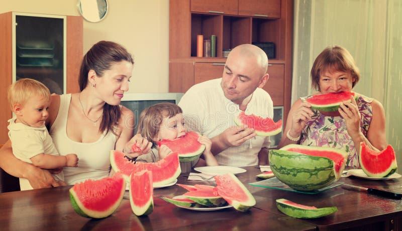 Lycklig familj samman med vattenmelon över att äta middag tabellen arkivbild