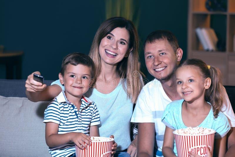 Lycklig familj som äter popcorn, medan hålla ögonen på TV i afton arkivfoto