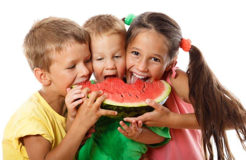 Lycklig familj som äter vattenmelon arkivfoton