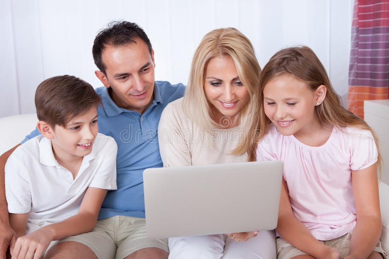 Lycklig familj som använder bärbar dator royaltyfri bild