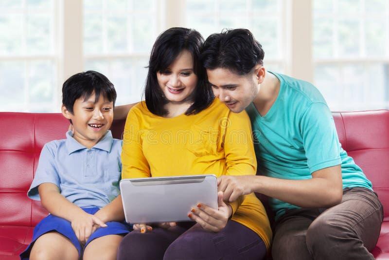 Lycklig familj som använder den digitala minnestavlan på soffan royaltyfria bilder