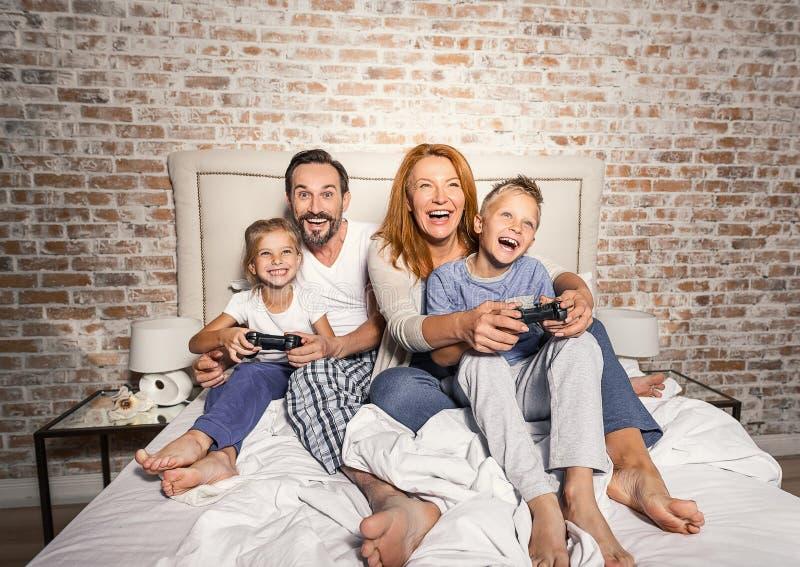 Lycklig familj som använder styrspakar och har gyckel royaltyfri foto