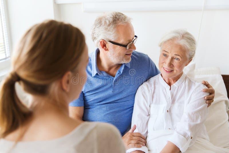 Lycklig familj som besöker den höga kvinnan på sjukhuset royaltyfri foto