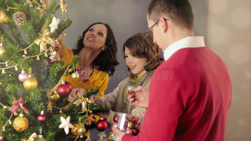 Lycklig familj som dekorerar julgranen som förbereder sig för ferie, festligt lynne arkivfoto