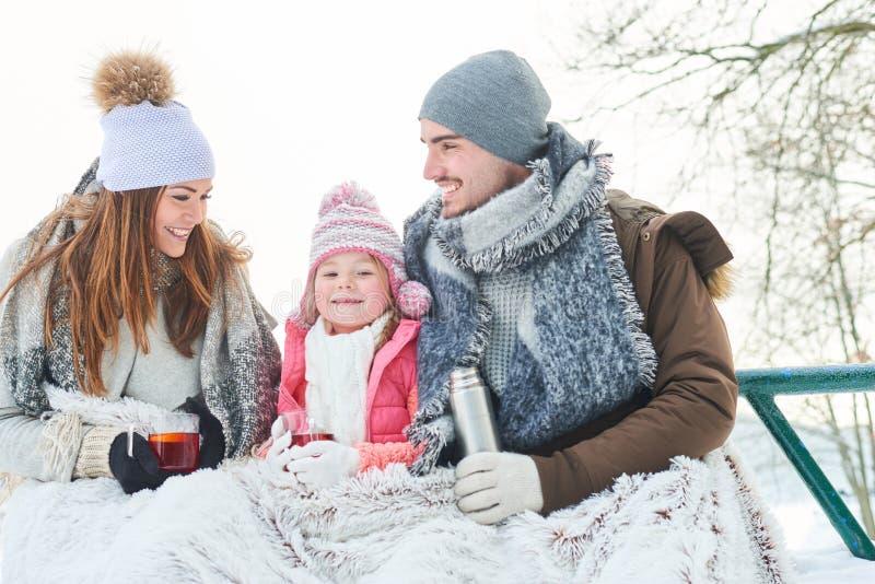 Lycklig familj som dricker te under vintertur royaltyfria foton