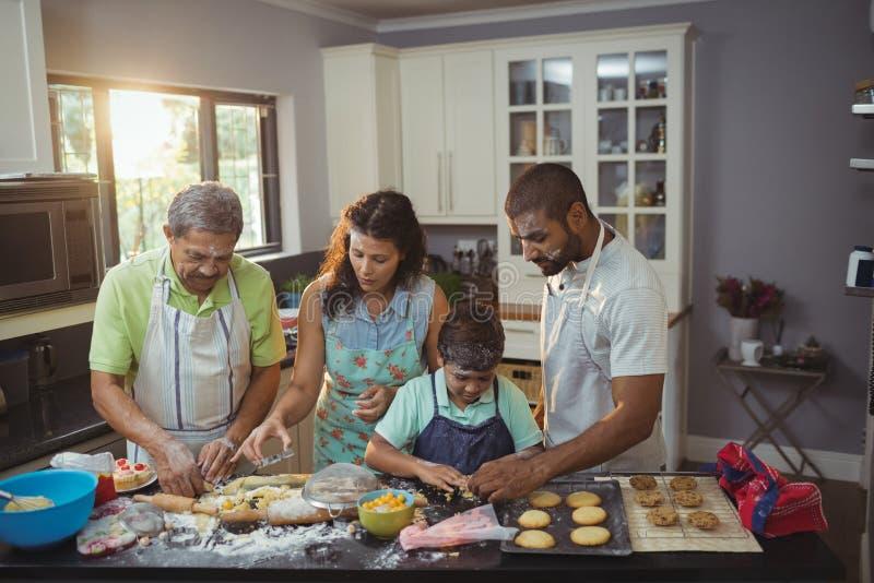 Lycklig familj som förbereder efterrätten i kök fotografering för bildbyråer