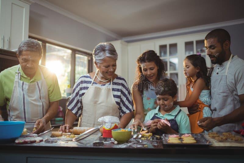 Lycklig familj som förbereder efterrätten i kök arkivfoton