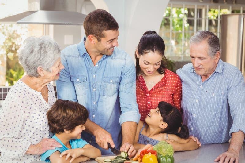 Lycklig familj som förbereder mat i kök arkivbilder