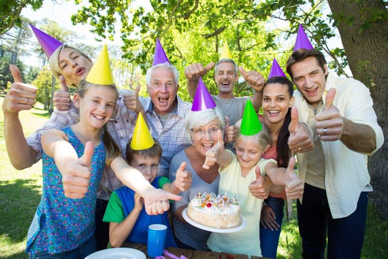Lycklig familj som firar en födelsedag med tummar upp arkivbild