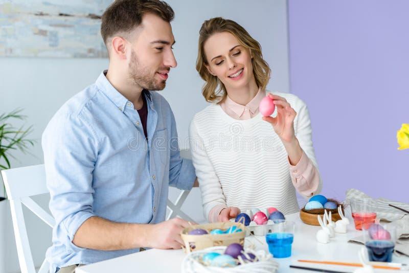 Lycklig familj som firar påsk med kulöra ägg royaltyfri foto