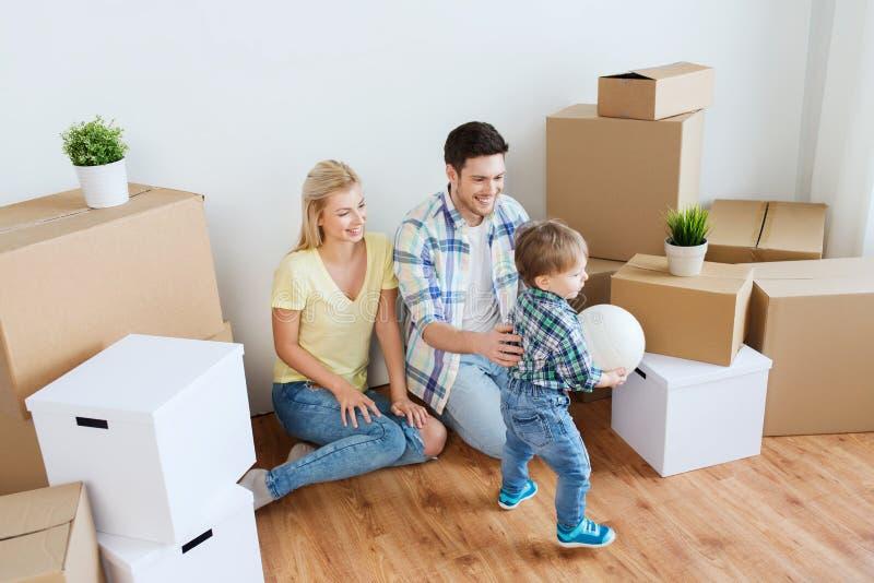 Lycklig familj som flyttar sig till det nya hemmet och spelar bollen arkivfoto