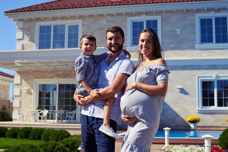 Lycklig familj som framme står av nytt modernt hus royaltyfri bild