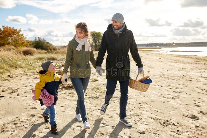 Lycklig familj som går att ha picknick på stranden i höst arkivfoto