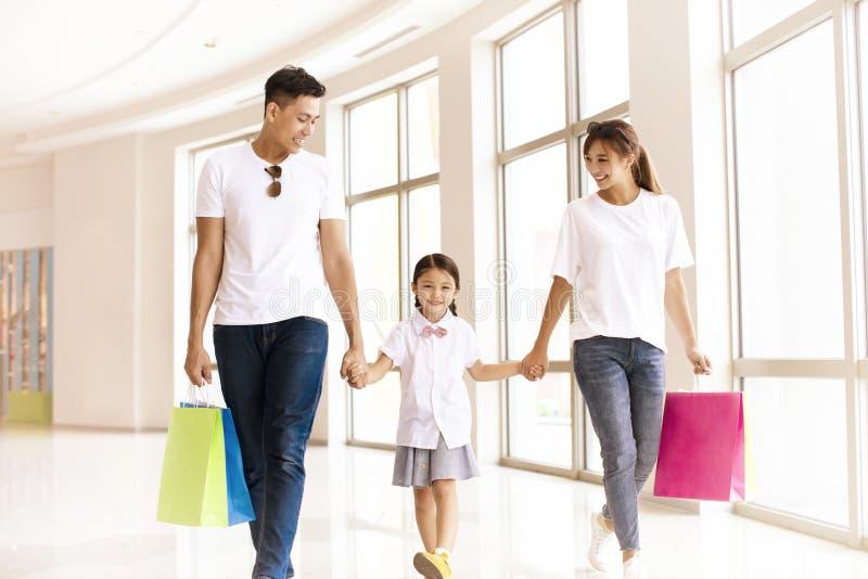 Lycklig familj som går i shoppinggallerian royaltyfria foton