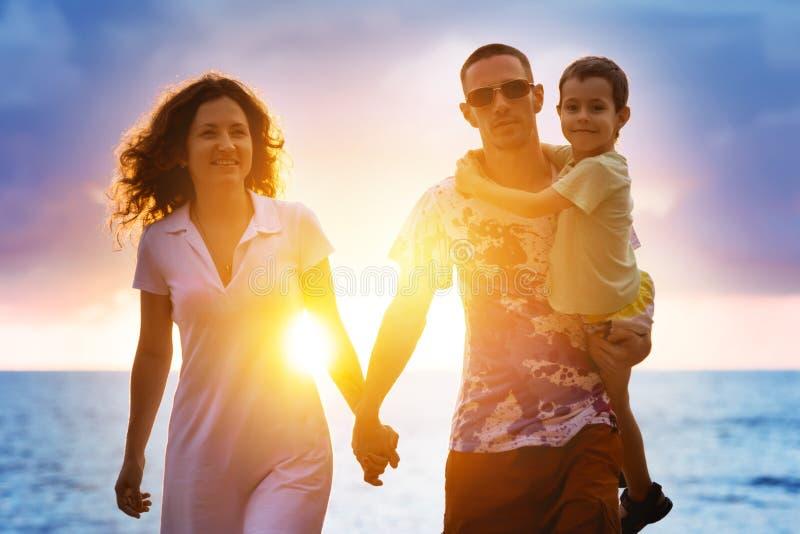 Lycklig familj som går på solnedgångstranden royaltyfria bilder