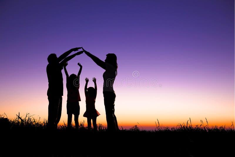 Lycklig familj som gör det hem- tecknet royaltyfri bild